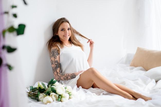Bella ragazza incinta in un abito bianco e con un mazzo di fiori. Foto Premium