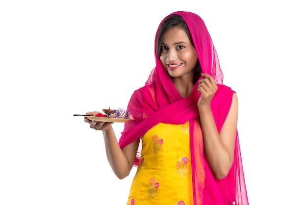 Bella ragazza indiana che tiene pooja thali o esecuzione di culto Foto Premium