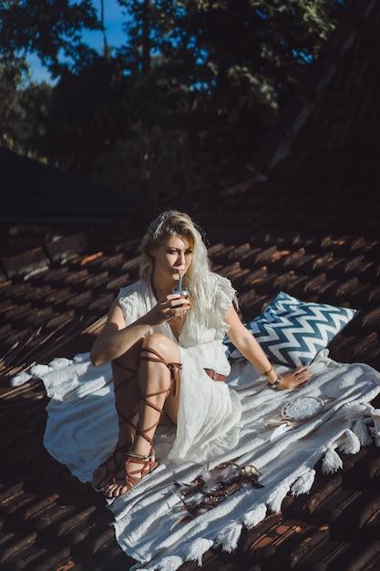 Bella ragazza indiana del hippie con capelli biondi lunghi sul tetto che beve il tè del compagno. Foto Gratuite