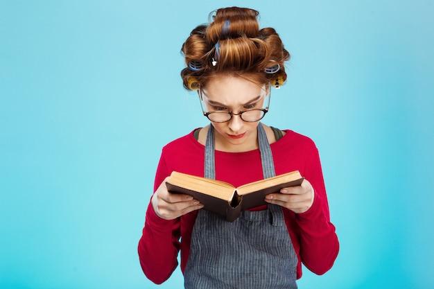 Bella ragazza legge libro con gli occhiali con i bigodini sui capelli Foto Gratuite