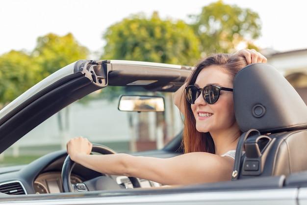Bella ragazza nell'automobile cabrio convertibile in una giornata di sole in una città Foto Premium