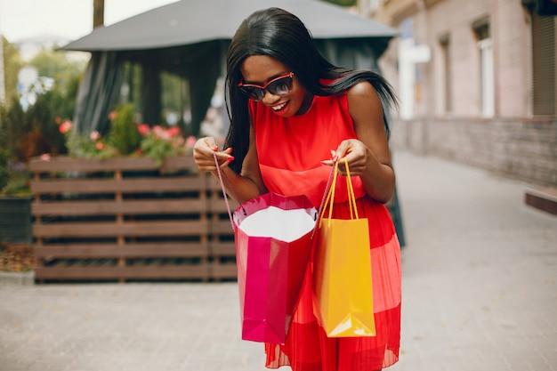 Bella ragazza nera con i sacchetti della spesa in una città Foto Gratuite