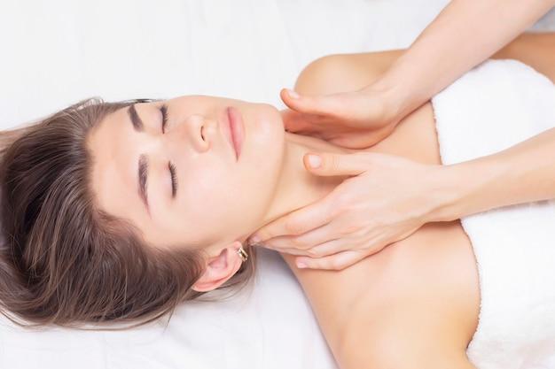 Bella ragazza ottiene massaggio in un salone spa. concetto di massaggio e salute. reumatismi, artrosi Foto Premium