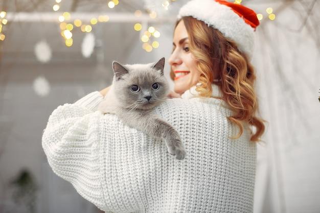 Bella ragazza seduta su un letto con gattino carino Foto Gratuite