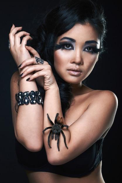 Bella ragazza sexy asiatica con ragno Foto Premium