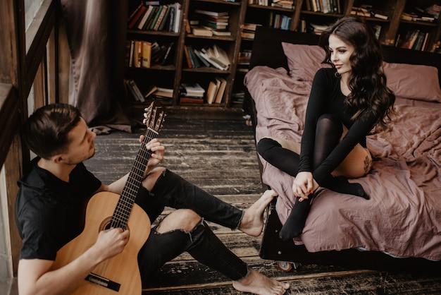 Bella ragazza sexy e il suo ragazzo a suonare la chitarra Foto Premium