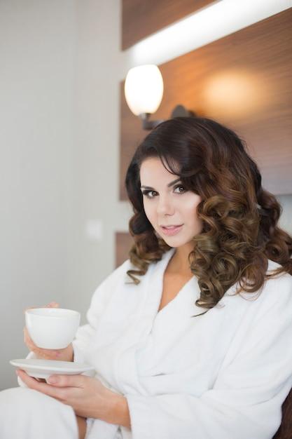 Bella ragazza sexy in accappatoio bianco con una tazza di caffè, Foto Premium