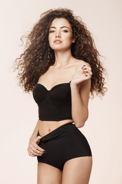 Bella ragazza sexy in retro biancheria intima nera sopra la parete rosa Foto Gratuite
