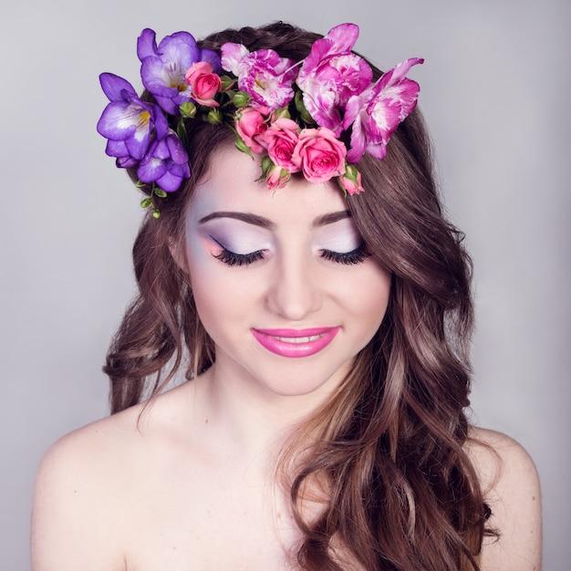 Bella ragazza sorridente con fiori tra i capelli Foto Premium