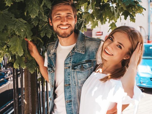 Bella ragazza sorridente e il suo ragazzo bello che posano nella via vicino all'albero. Foto Gratuite