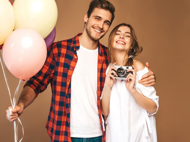 Bella ragazza sorridente e il suo ragazzo bello che tiene mazzo di palloncini colorati. coppie felici che prendono il selfie della foto di se stessi sulla retro macchina fotografica. buon compleanno Foto Gratuite