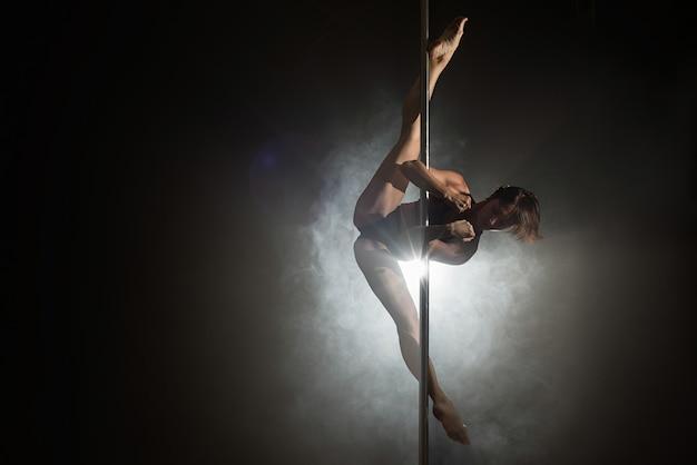 Bella ragazza sottile con pilone ballerino del palo femminile ballando Foto Premium