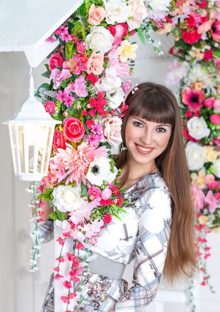 Bella ragazza sotto il portico con lanterna bianca e fiori Foto Premium