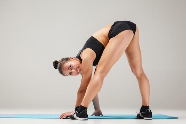 Bella ragazza sportiva che sta nella posa dell'acrobata o nel asana di yoga Foto Gratuite