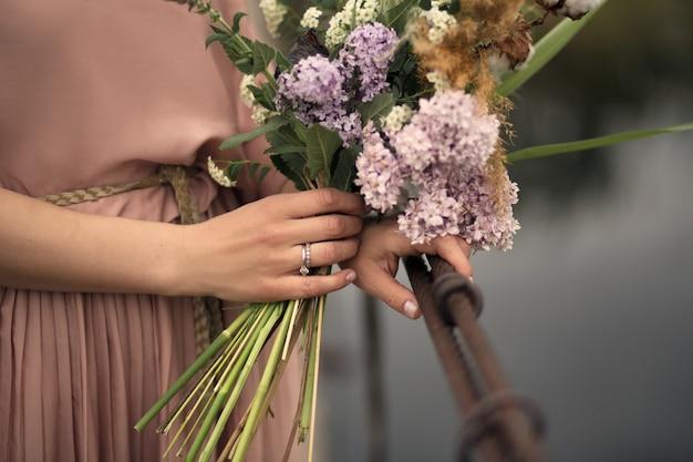 Bella ragazza tenera in un vestito color pesca che cammina su un ponte di legno rurale con un mazzo di fiori in mano Foto Premium