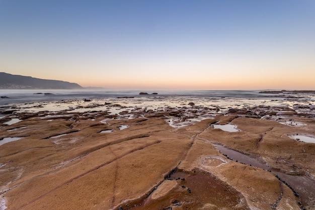Bella ripresa dall'alto della terra vicino al corpo dell'acqua dell'oceano la sera Foto Gratuite