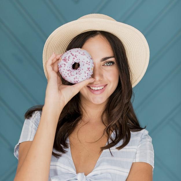 Bella signora che copre l'occhio con una ciambella Foto Gratuite