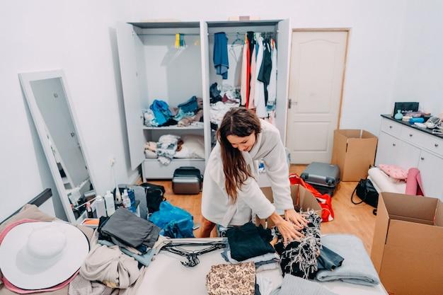 Bella signora dall'aspetto moderno nell'appartamento moderno si prepara al viaggio Foto Gratuite