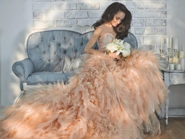 Bella signora in abito couture splendido sul divano Foto Premium