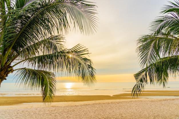 Bella spiaggia dell'oceano del mare con la palma a tempo di alba per la festa Foto Gratuite