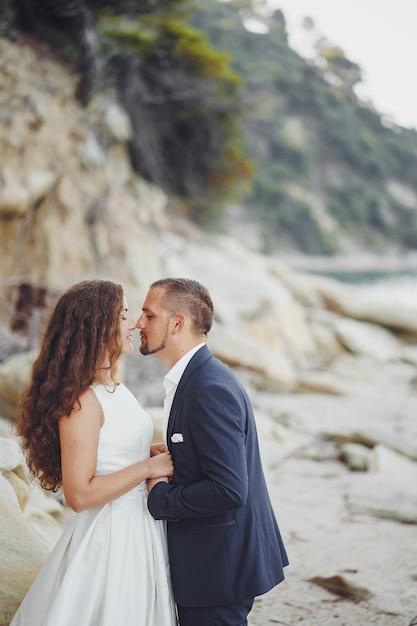 Bella sposa dai capelli lunghi in abito bianco con il marito sulla spiaggia vicino a grandi pietre Foto Gratuite