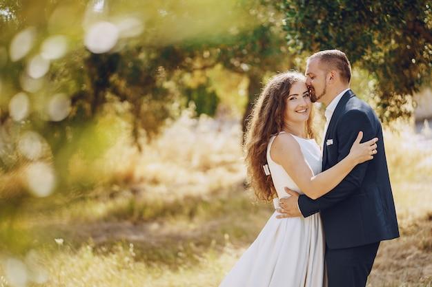 Bella sposa dai capelli lunghi in abito bianco con il suo giovane a piedi nella natura Foto Gratuite