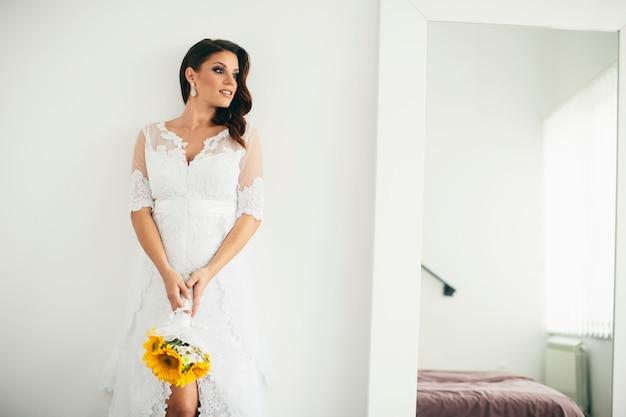 Bella sposa in posa in un abito da sposa e in possesso di un mazzo di girasole Foto Premium
