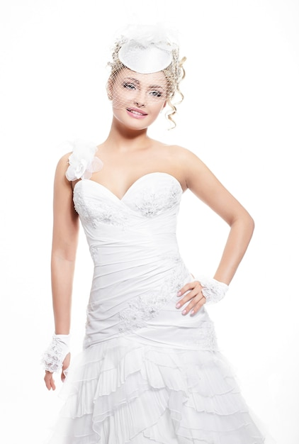 Bella sposa sorridente felice in abito da sposa bianco con acconciatura e trucco luminoso Foto Gratuite