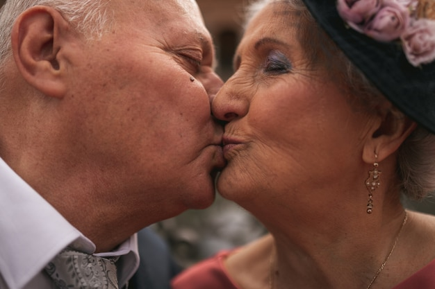 Bella stretta di una coppia di anziani nel giorno del loro matrimonio d'oro baciarsi in bocca. anziani felici. Foto Premium