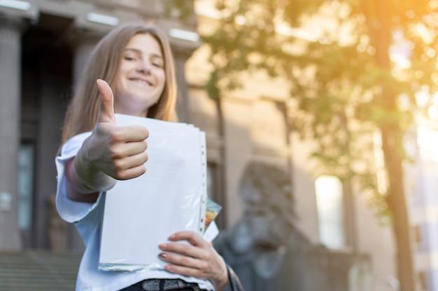 Bella studentessa in piedi vicino all'università, con in mano una carta che sorride e che mostra come al college, va a scuola Foto Premium