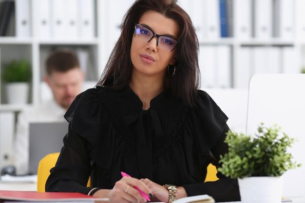 Bella tenuta sorridente della donna del brunette nella penna dentellare di braccia Foto Premium