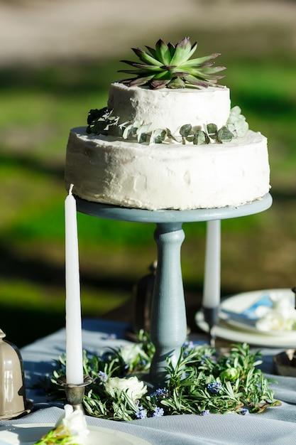 Bella torta nunziale bianca con i fiori all'aperto Foto Premium