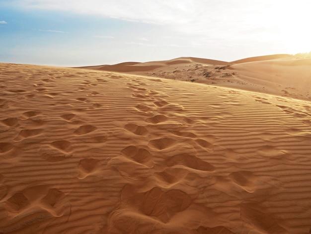 Bella vista delle dune di sabbia con trama di stampe. impronta che scavalca la duna di sabbia. Foto Premium