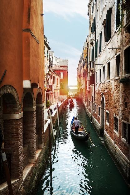 Bella vista sul canale d'acqua veneziana con gondolier e barca. venezia, italia. Foto Gratuite