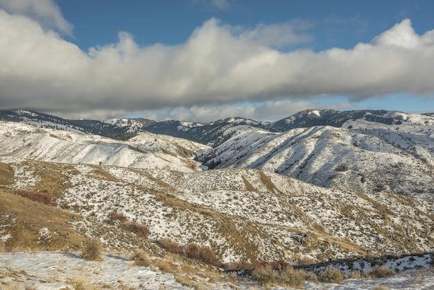Bella vista sulle montagne innevate con un cielo nuvoloso blu durante il giorno Foto Gratuite