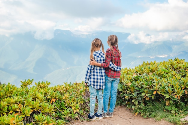 Belle bambine felici in montagna sullo sfondo della nebbia Foto Premium