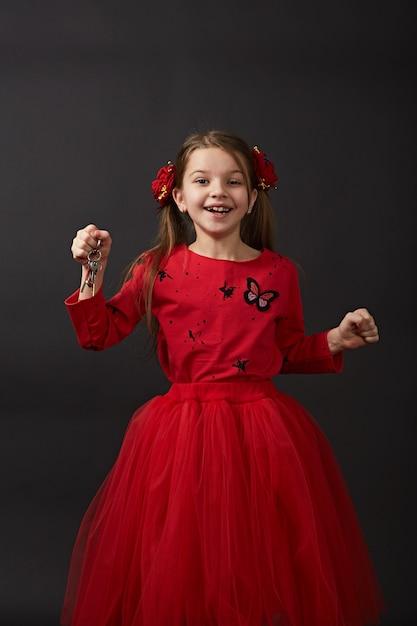 Belle chiavi caucasiche dell'automobile della tenuta della ragazza, appartamento. un bambino in abiti rossi è molto felice Foto Premium