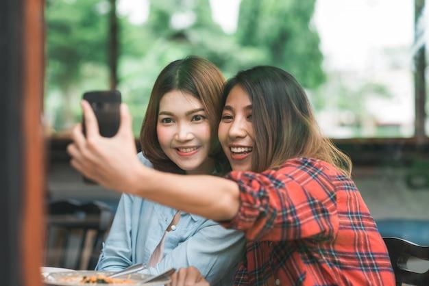 Belle coppie asiatiche felici delle donne asiatiche lgbt che si siedono ogni lato che mangia un piatto di frutti di mare italiani Foto Gratuite