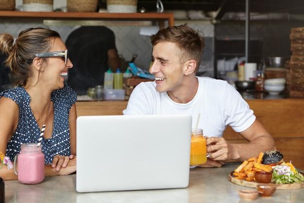 Belle coppie che hanno conversazione vivace che si siede alla tavola con il computer portatile e l'alimento nell'interno accogliente della caffetteria Foto Gratuite