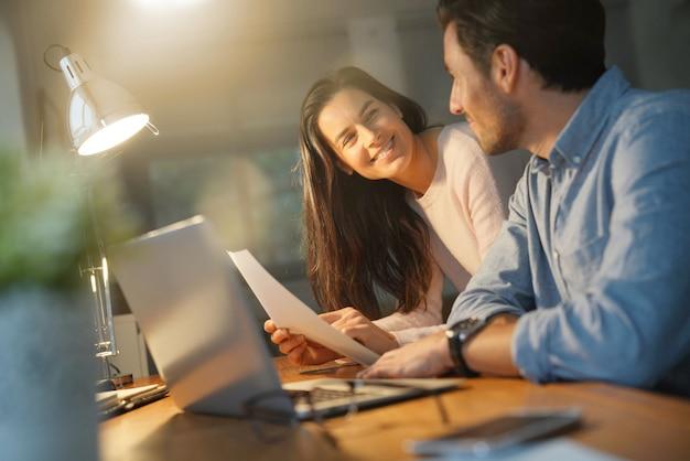Belle coppie che lavorano sul computer condiviso a casa Foto Premium