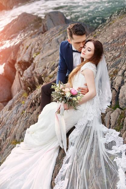 Belle coppie nell'amore che bacia seduta sulle rocce Foto Premium