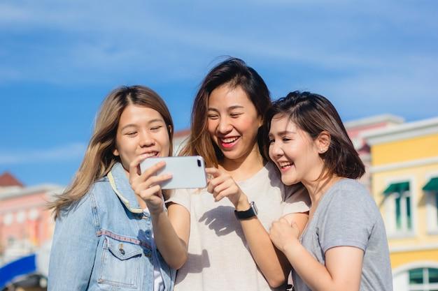 Belle donne asiatiche attraenti degli amici che per mezzo di uno smartphone Foto Gratuite