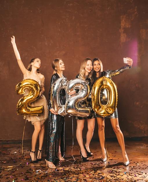 Belle donne che celebrano il nuovo anno belle ragazze felici in eleganti abiti da festa sexy con palloncini d'oro e d'argento 2020, divertendosi alla festa di san silvestro. facendo selfie o video per instagram Foto Gratuite