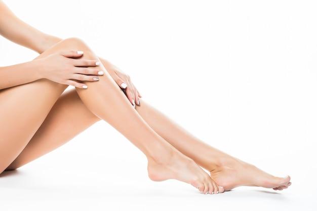 Belle gambe femminili, corpo posteriore dell'asino isolato sopra la parete bianca che si trova sul pavimento con il concetto di cura della pelle lunga gamba, spa e bellezza. Foto Gratuite