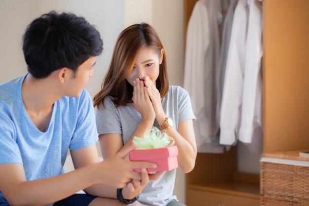 Belle giovani coppie asiatiche nell'amore con il contenitore di regalo di sorpresa Foto Premium