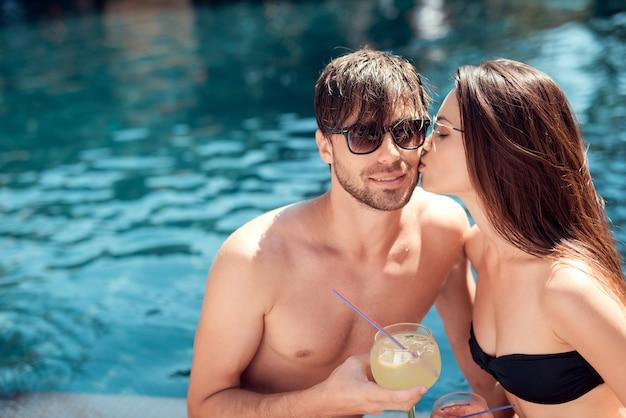 Belle giovani coppie che tengono i vetri con alcolici Foto Premium
