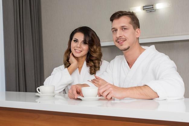 Belle giovani coppie della famiglia in accappatoi bianchi che godono della luna di miele all'hotel Foto Premium