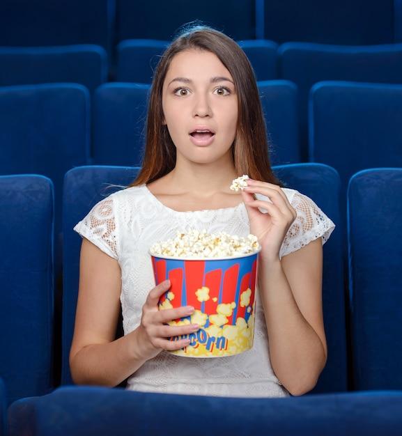 Belle giovani donne che mangiano popcorn. Foto Premium