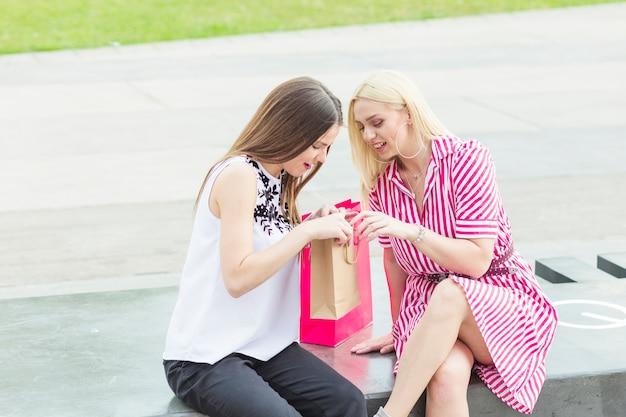 Belle giovani donne con i suoi amici guardando nella borsa della spesa Foto Gratuite