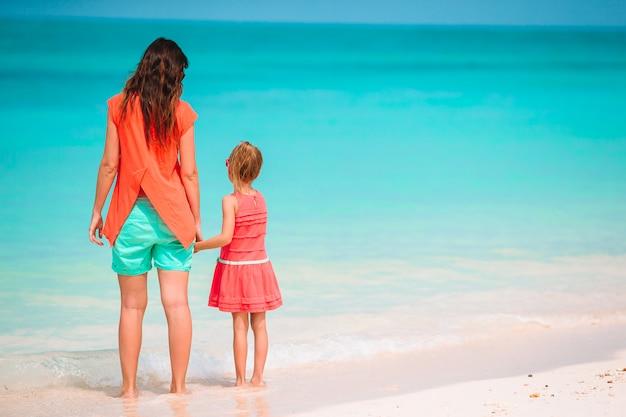 Belle madre e figlia alla spiaggia caraibica che godono delle vacanze estive. Foto Premium